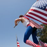 Young man on unicycle with American flag. People at Morro Bay, C
